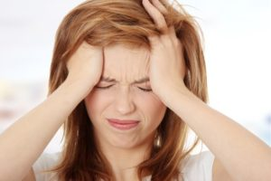 Person holding head with migraine headache pain